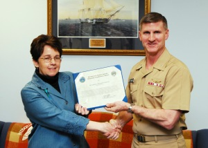 Commander Navy Region Northwest, Rear Adm. Mark Rich, presents NAS Whidbey Island's Kathleen Schofield an award as the DoD Sexual Assault Response Coordinator of the Year, April 19.