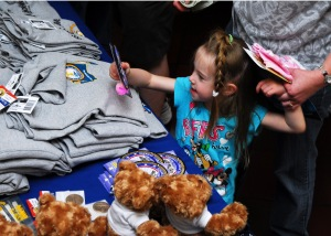 "A Family member receives a gift at the Naval Base Kitsap Recreation Gym, May 2, during the USS John C. Stennis ""Night Before"" party. Stennis returns to her homeport of Bremerton, Wash., May 3. Photo by MCC Eric Harrison"