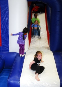 "Family members slide down the bounce house at the Naval Base Kitsap Gym, May 2, during the USS John C. Stennis ""Night Before"" party. Stennis returns to her homeport of Bremerton, Wash., May 3. Photo by MCC Eric Harrison"