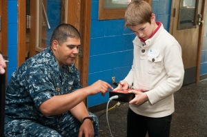 BREMERTON, Wash. (June 01, 2013) Chief Sonar Technician (Submarine) German Sotelo, assigned to Submarine Development Squadron Five, shows a middle school student how to use the remote for a Navy remote operated vehicle (ROV) at the 2nd annual ROV challenge at Olympic High School Aquatics Facility. The competition allows students to apply science, technology, engineering, and mathematics skills while building remotely operated vehicles to perform tasks underwater. (U.S. Navy photo by Mass Communication Specialist 3rd Class Chris Brown/Released)