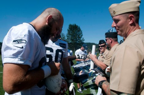 RENTON, Wash. (August 21, 2013) Chief Boatswain's Mate Jason Sowell, assigned to Afloat Training Group at Naval Station Everett, receives an autograph from Seattle Seahawks Tight End Sean McGrath after a team in Renton, Wash. The Seahawks hosted more than 100 Sailors for their practice and a meet and greet with the players. (U.S. Navy photo by Mass Communication Specialist 2nd Class Justin A. Johndro/Released)