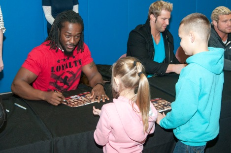 "SILVERDALE, Wash. (Dec. 11, 2013) Kofi Kington, World Wrestling Entertainment (WWE) wrestler, signs autographs for Sailors and their families at Naval Base Kitsap Bangor in celebration of ""Tribute for the Troops"". WWE athletes visited military installations throughout the Pacific Northwest as part of their 10th annual ""Tribute to the Troops"" performance at Joint Base Lewis-McChord, which will air on Dec. 19 and Dec. 28. WWE Tribute to the Troops is an annual event held by WWE with Armed Forced Entertainment as a way of honoring the men and women of the Armed Forces. (U.S. Navy photo by Mass Communication Specialist Seaman William Blees/Released)"