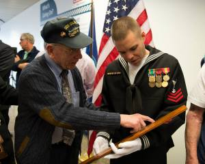"Navy veteran, EM1 Larry ""Sparks"" Clements (92) points out burn marks on a plank of teak decking from a kamikaze attack aboard USS Colorado (BB45) during WWII to NC1 William McKenna during a deck transfer ceremony between Boeing and the USO at Sea-Tac airport. The teak deck, originally from the deck of the battleship USS Colorado (BB45), had been purchased by Boeing in 1959 and was on display on the walls of the Boeing cafeteria. The wood deck will now be installed as flooring in the Sea-Tac airport USO currently undergoing renovation and due to open later this year. Photo by MCC John Lill"
