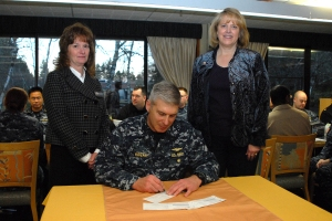 SILVERDALE, Wash. (Feb. 13, 2014) Capt. Scott Hogan, Navy Region Northwest chief of staff, and native of Rutland, Vt., signs the first enrollment donation forms for the Navy and Marine Relief Corps Society (NMCRS) fund drive during the annual kick-off breakfast at the Trident Inn Galley on Naval Base Kitsap Bangor. NMCRS was established in 1904 to aid Sailors and Marines in financial duress. (U.S. Navy photo by Mass Communication Specialist 2nd Class Cory Asato/Released)