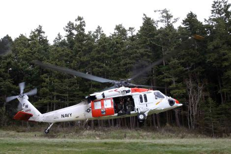 140325-N-DC740-010 OAK HARBOR, Wash. (March 25, 2014) An MH-60 Seahawk helicopter assigned to Naval Air Station Whidbey Island's (NASWI) Search and Rescue (SAR) unit takes off from a training area near NASWI. The SAR team provides assistance to military and civilians throughout the Pacific Northwest. (U.S. Navy photo by Mass Communication Specialist 2nd Class John Hetherington)