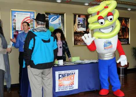 The Navy Shore Energy Program official mascot BRITE, far right, welcomes Navy Region Northwest employees to a Region All Hands Call Mar. 27, where BRITE and Region Commander Rear Adm. Bette Bolivar will speak about the importance of energy conservation and ways to reduce energy consumption. BRITE and other Naval Facilities Engineering Command Northwest employees handed out informational material about energy efficiency to employees before and after the All Hands Call. BRITE was created in 2008 in the Navy's Northwest region, and more recently became the official mascot for the Navy's entire Shore Energy Program.  (U.S. Navy photo by Liane Nakahara)