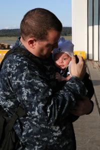 "OAK HARBOR, Wash. (April 19, 2014) Aviation Ordnanceman 1st Class Matthew Sweatt, from San Dimas, Calif., assigned to the ""Zappers"" of Electronic Attack Squadron (VAQ) 130, holds his son for the first time during a homecoming celebration at Naval Air Station Whidbey Island. The Zappers are returning from a nine-month deployment to the 5th Fleet area of responsibility in support of Operation Enduring Freedom embarked aboard the aircraft carrier USS Harry S. Truman (CVN 75). The Zappers are the second carrier based squadron to deploy with the EA-18G Growler. (U.S. Navy photo by Mass Communication Specialist 2nd Class John Hetherington)"