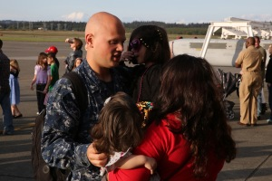 "OAK HARBOR, Wash. (April 19, 2014) Aviation Structural Mechanic 3rd Class Ryan Risatti, from Princeton, Ill., assigned to the ""Zappers"" of Electronic Attack Squadron (VAQ) 130, greets his wife and daughters during a homecoming celebration at Naval Air Station Whidbey Island. The Zappers are returning from a nine-month deployment to the 5th Fleet area of responsibility in support of Operation Enduring Freedom embarked aboard the aircraft carrier USS Harry S. Truman (CVN 75). The Zappers are the second carrier based squadron to deploy with the EA-18G Growler. (U.S. Navy photo by Mass Communication Specialist 2nd Class John Hetherington)"