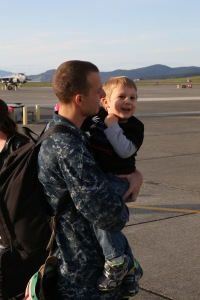 "OAK HARBOR, Wash. (April 19, 2014) Aviation Electrician's Mate 2nd Class Jarrod Langford, from Orlando, Fla., assigned to the ""Zappers"" of Electronic Attack Squadron (VAQ) 130, holds his son during a homecoming celebration at Naval Air Station Whidbey Island. The Zappers are returning from a nine-month deployment to the 5th Fleet area of responsibility in support of Operation Enduring Freedom embarked aboard the aircraft carrier USS Harry S. Truman (CVN 75). The Zappers are the second carrier based squadron to deploy with the EA-18G Growler. (U.S. Navy photo by Mass Communication Specialist 2nd Class John Hetherington)"