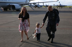 "OAK HARBOR, Wash. (April 19, 2014) Aviation Electronics Technician 2nd Class Jonathon Daniels, from Phoenix, assigned to the ""Zappers"" of Electronic Attack Squadron (VAQ) 130, walks with his daughter and wife during a homecoming celebration at Naval Air Station Whidbey Island. The Zappers are returning from a nine-month deployment to the 5th Fleet area of responsibility in support of Operation Enduring Freedom embarked aboard the aircraft carrier USS Harry S. Truman (CVN 75). The Zappers are the second carrier based squadron to deploy with the EA-18G Growler. (U.S. Navy photo by Mass Communication Specialist 2nd Class John Hetherington)"