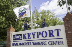 Captain David Kohnke (R), commanding officer of Naval Undersea Warfare Center Division, Keyport (NUWC Keyport), looks on as  Commander Dustin Demorest, chief staff officer of NUWC Keyport, raises their command's centennial commemorative flag on June 27 at Naval Base Kitsap-Keyport (NBK-Keyport). The flag, suggested by NUWC Keyport employee Wayne Jordheim, will be flown at NBK-Keyport through the end of 2014 as a reminder of the important contributions the men and women of NUWC Keyport have made to national defense over the past 100 years. Photo by Bre Zinter, Keyport Photographer, McLaughlin Research Corporation.