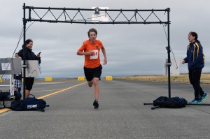 140719-N-DC740-030 OAK HARBOR, Wash. (July 19, 2014) Dylan Holland, a student at Anacortes High, finishes the 5k run on the base flight line in 1st place with a time of 17 minutes and 38 seconds during Naval Air Station Whidbey Island's (NASWI) open house. The open house provides the general public an opportunity to interact with Sailors and learn more about NASWI's role both in the community and the Navy. (U.S. Navy photo by Mass Communication Specialist 2nd Class John Hetherington)