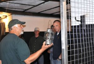 Before there was electricity at Fort Casey, Fort Casey historian Dave Kobylk explains that lanterns were used at the encampment. Seen on the tour are Capt. Michael Nortier, base wildlife biologist John Phillips and Cmdr. Richard Stevens, NAS Whidbey Island Executive Officer.