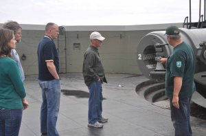 Fort Casey historian Dave Kobylk describes characteristics of the gun battery and its disappearing carriage to NAS Whidbey Island employees Allison Crain, John Phillips, Cmdr. Steven Richards and Capt. Michael Nortier before the Navy volunteers took on a restoration project.