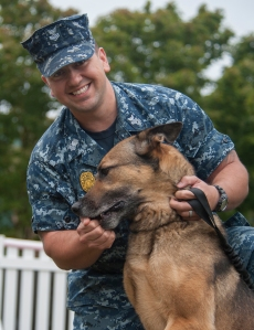 140924-N-MM360-018 EVERETT, Wash. (Sept. 24, 2014) – Master-at-Arms 1st Class Fabian Salazar, a native of El Paso, Texas, gives a treat to military working dog Max at Naval Station Everett's (NSE) military working dog kennel.  Salazar worked as Max's handler during an individual augmentee deployment to Afghanistan, where he received an Army Commendation Medal with Valor for his bravery during combat.  (U.S. Navy photo by Mass Communication Specialist 2nd Class Jeffry A. Willadsen/Released)