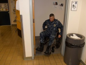 141007-N-MN975-021 SILVERDALE, Wash. (October 7, 2014) - Cmdr. Nick Yamodis, Naval Facilities Engineering Command Northwest (NAVFAC) operations officer, transits through the bathroom door in a wheelchair during National Disability Employment Awareness month. Navy Region Northwest participated in a disability awareness exercise putting Sailors in an impaired state to help expand the awareness for those who are disabled. (U.S. Navy photo by Mass Communication Specialist 2nd Class Justin A. Johndro/RELEASED)