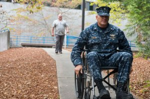 141007-N-MN975-028 SILVERDALE, Wash. (October 7, 2014) - Cmdr. Nick Yamodis, Naval Facilities Engineering Command Northwest (NAVFAC) operations officer, transits on the sidewalk in a wheelchair during National Disability Employment Awareness month. Navy Region Northwest participated in a disability awareness exercise and putting Sailors in an impaired state to help expand the awareness for those who are disabled. (U.S. Navy photo by Mass Communication Specialist 2nd Class Justin A. Johndro/RELEASED)