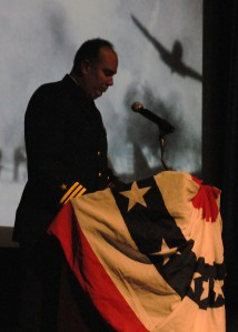 141207–N-ZY850-024 KEYPORT, Wash. (Dec. 7, 2014) Cmdr. Dustin Demorest, Naval Undersea Warfare Center chief of staff, narrates the events of the Pearl Harbor attack at a remembrance ceremony at the Naval Undersea Warfare Center Jack Murdock Auditorium. The ceremony honored the 2,403 Americans who died during the Japanese attack on Pearl Harbor on Dec. 7, 1941. (U.S. Navy photo by Mass Communication Specialist 2nd Class Jamie Hawkins/Released)