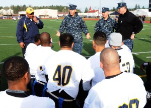 141212-N-ZY850-006 TACOMA, Wash. (Dec. 12, 2014) Capt. Thomas Zwolfer, Naval Base Kitsap commanding officer (center), speaks with Team Navy prior the 15th annual Army vs. Navy flag football game at Joint Base Lewis-McChord's Cowan Stadium in Tacoma, Wash., Dec. 12. Navy defeated Army 24-9. (U.S. Navy photo by Mass Communication Specialist 2nd Class Jamie Hawkins/Released)