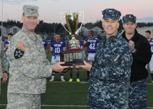 141212-N-ZY850-065 TACOMA, Wash. (Dec. 12, 2014) Col. H. Charles Hodges, Commander, Joint Base Lewis-McChord (left), gives Capt. Thomas Zwolfer, Naval Base Kitsap commanding officer (right), the game trophy after the 15th annual Army vs. Navy flag football game at Joint Base Lewis-McChord's Cowan Stadium in Tacoma, Wash., Dec. 12. Navy defeated Army 24-9. (U.S. Navy photo by Mass Communication Specialist 2nd Class Jamie Hawkins/Released)