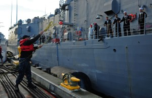 141219-N-MM360-196 EVERETT, Wash. (Dec. 19, 2014) – A Sailor throws a line to Sailors aboard the Oliver Hazard Perry-class guided-missile frigate USS Rodney M. Davis (FFG 60) as the ship moors at its homeport of Naval Station Everett (NSE). Rodney M. Davis returned from its final deployment to the Western Pacific and Indian Ocean to her homeport at Naval Station Everett Dec. 19 and will prepare to decommission in 2015. (U.S. Navy photo by Mass Communication Specialist 1st Class Jeffry A. Willadsen/Released)