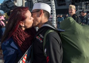 141219-N-MN975-029 EVERETT, Wash. (Dec. 19, 2014) Cryptologic Technician (Technical) 2nd Class Carlos Villareal, a native of San Diego assigned to the Oliver Hazard Perry-class guided-missile frigate USS Rodney M. Davis (FFG 60), kisses his wife Janet after completing a six-month deployment. Rodney M. Davis returned from its final deployment to the Western Pacific and Indian Ocean to her homeport at Naval Station Everett Dec. 19 and will prepare to decommission in 2015. (U.S. Navy photo by Mass Communication Specialist 2nd Class Justin A. Johndro/RELEASED)