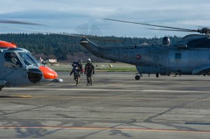 """150324-N-WQ574-149 OAK HARBOR, Wash. (March 24, 2015) Hospitalman John Siedler, from Jackson, N.J., assigned to Naval Air Station Whidbey Island (NASWI) Search and Rescue (SAR), carries """"Rescue Randy,"""" a training dummy, from a Royal Canadian Air Force (RCAF) CH-124 Sea King to a SAR MH-60S Knighthawk during a joint training exercise at NASWI. RCAF and SAR perform biannual training to enhance cooperation for joint rescue efforts. (U.S. Navy photo by Mass Communication Specialist 3rd Class Caleb Cooper/Released)"""
