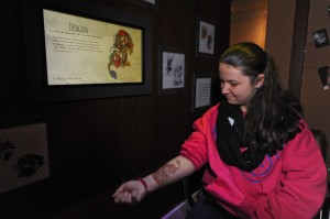 "150403-N-OO032-024 BREMERTON, Wash. (April 3, 2015) -- Sawyer Cranston, a patron visiting from Chicago, uses an interactive display by selecting a Sailor tattoo to be projected on her forearm while sitting in a dental chair at the Puget Sound Navy Museum's naval heritage tattoo exhibit ""Skin Deep: The Nautical Roots of Tattoo Culture."" The exhibit showcases how the history of Sailors and nautical culture in the U.S. and British Royal Navies are closely intertwined from the 1800s through the present. (U.S. Navy photo by Mass Communication Specialist 2nd Class Cory Asato/Released)"