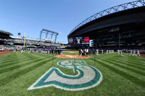 """150419-N-OO032-054 SEATTLE (April 19, 2015) -- Seattle Mariners and Texas Rangers join service members on the field for the """"National Anthem"""" during the Seattle Mariners' 14th Annual Salute to Armed Forces at Safeco Field. A service member representing each of the five armed services threw a ceremonial first pitch. (U.S. Navy photo by Mass Communication Specialist 2nd Class Cory Asato/Released)"""