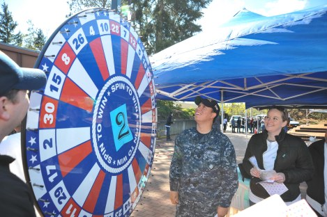 """150424-N-EC099-050 SILVERDALE, Wash. (April 24, 2015) -- Naval Hospital Bremerton Sailors facilitate a """"Spin the Wheel and learn the Spectral of Harm"""" activity booth during Naval Base Kitsap's Annual Sexual Assault Prevention and Response Carnival in recognition of Sexual Assault Awareness Month at Naval Base Kitsap - Bangor. The carnival featured multiple activity booths to educate fairgoers on the hardships faced by survivors of sexual assault and harassment. (U.S. Navy Photo by Mass Communication Specialist 3rd Class Charles W. Gaddis IV/Released)"""