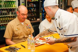 150509-N-EC099-102 BREMERTON, Wash. (May 9, 2015) – Culinary Specialist 2nd Class Lawrence Jasper, assigned to Naval Base Kitsap-Bangor, serves Capt. John Ring, commanding officer of USS Nimitz, a dish during the 23rd Annual Armed Forces Culinary Arts Competition. The Armed Forces Culinary Arts Competition is held to increase the morale of service members and bring the civilian and military closer together. (U.S. Navy Photo by Mass Communication Specialist 3rd Class Charles W. Gaddis IV/Released)