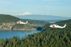 (FILE PHOTO) 140116-N-ZF573-184 OAK HARBOR, Wash. (Jan. 16, 2014) Two MH-60 Sea Hawk helicopters from Naval Air Station Whidbey Island's Search and Rescue (SAR) fly in formation during a training operation in the Pacific Northwest. The SAR team provides assistance to military and civilians throughout the Pacific Northwest. (U.S. Navy photo by Mass Communication Specialist 2nd Class Chris Brown/Released)