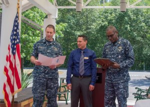 150611-N-LQ926-026 MARYSVILLE, Wash. (June 11,2015) Capt. James Watts, deputy commander military services, and Cmdr. James Caulk, Naval Station Everett (NSE) executive officer, present Dominic Lewis, Navy Lodge Everett general manager, with the Carlson Award during a ceremony held at the NSE Support Complex at Smokey Point. The Edward E. Carlson Award is presented to the Navy Lodge that demonstrates superior performance throughout the year. (U.S. Navy photo by Mass Communication Specialist 2nd Class Alex Van'tLeven/Released)