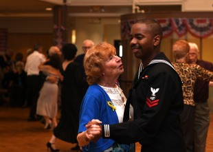 EVERETT, Wash. (Nov. 11, 2016) Petty Officer 2nd Class Jermonte T. Smith, assigned to Naval Station Everett (NSE), dances with a patron during the 11th Annual Veterans Day United Service Organizations dance at the Carl Gibson Senior Center in Everett. Each year Sailors from NSE are invited to volunteer and attend the Veterans Day event. (U.S. Navy photo by Petty Officer 2nd Class Alex Van'tLeven/Released)
