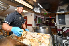 170502-N-EC099-053 SILVERDALE, Wash. (May 2, 2017) Culinary Specialist 2nd Class Kevin Miller, assigned to Naval Base Kitsap's Trident Inn Galley, removes seasoned chicken from the kettle in preparation of lunch. Culinary Specialists operate and manage dining facilities and living quarters for Sailors and Marines in the U.S. Navy. (U.S. Navy photo by Mass Communication Specialist 3rd Class Charles D. Gaddis IV/Released)