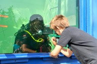 170916-N-EC099-074 KEYPORT, Wash. (Sept. 16, 2017) - Navy Diver 2nd Class Dirk Hanous, assigned to Naval Undersea Warfare Center-Keyport, plays tic-tac-toe with children during Keyport's annual 2017 Keyport Fest celebration. Keyport Fest, hosted by the Keyport Improvement Club, is open to all and increases the morale and connection between Keyport and its surrounding communities. (U.S. Navy photo by Mass Communication Specialist 3rd Class Charles D. Gaddis IV/Released)