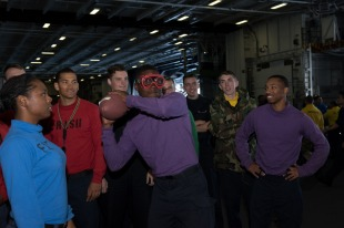 "170917-N-ZU663-023 PACIFIC OCEAN (Sept. 17, 2017) Airman Brandon Westbrook, from Cleveland, Ohio, throws a football while wearing goggles to simulate the effects of alcohol during a ""Tackle the DUI"" tailgating event in the hangar bay aboard USS John C. Stennis (CVN 74). John C. Stennis is underway training for future operations after completing flight deck certification and carrier qualifications. (U.S. Navy photo by Mass Communication Specialist 2nd Class Susan C. Damman/Released)"