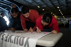 "170917-N-ZU663-034 PACIFIC OCEAN (Sept. 17, 2017) Sailors sign a banner pledging to never drink and drive during a ""Tackle the DUI"" tailgating event in the hangar bay aboard USS John C. Stennis (CVN 74). John C. Stennis is underway training for future operations after completing flight deck certification and carrier qualifications. (U.S. Navy photo by Mass Communication Specialist 2nd Class Susan C. Damman/Released)"