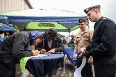 170920-N-VH385-205 JOINT BASE LEWIS-MCCHORD, Wash. (Sept. 19, 2017) Members of the Seattle Seahawks sign autographs for Sailors during the 6th annual USAA Change of Command ceremony at Joint Base Lewis-McChord. This year the Seattle Seahawks and USAA presented the Army's 1st Special Forces Group with the 12th Man Flag, following a season of Navy Region Northwest carrying to flag. (U.S. Navy photo by Mass Communication Specialist 2nd Class Wyatt L. Anthony)