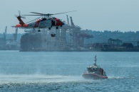 180731-N-SH284-0284 SEATTLE (July 31, 2018) A U.S. Coast Guard MH-60T Jayhawk Helicopter performs a mock rescue during a search and rescue demonstration over Elliott Bay as part of the 69th annual Seafair Fleet Week. Seafair Fleet Week is an annual celebration of the sea services wherein Sailors, Marines and Coast Guard members from visiting U.S. Navy and Coast Guard ships and ships from Canada make the city a port of call. (U.S. Navy photo by Mass Communication Specialist 2nd Class Vaughan Dill/Released)