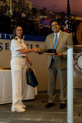 180801-N-SH284-1062 SEATTLE (Aug. 1, 2018) Cmdr. Elaine Brunelle, commanding officer, USS Momsen (DDG 92), presents Seattle Deputy Mayor Mike Fong with a plaque and a command ball cap at the Seattle Mayor's reception during the 69th annual Seafair Fleet Week. Seafair Fleet Week is an annual celebration of the sea services wherein Sailors, Marines and Coast Guard members from visiting U.S. Navy and Coast Guard ships and ships from Canada make the city a port of call. (U.S. Navy photo by Mass Communication Specialist 2nd Class Vaughan Dill/Released)