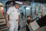 180802-N-DA737-0270 SEATTLE (Aug. 2, 2018) Joe Savage, Port of Seattle Police Department Chief for a Day, mans the helm of amphibious transport dock ship USS Somerset (LPD 25) with Capt. Brian Quin, commanding officer of Somerset. Somerset is in port in Seattle for Seafair Fleet Week, an annual celebration of the sea services wherein Sailors, Marines and Coast Guard members from visiting U.S. Navy and Coast Guard ships and ships from Canada make the city a port of call. (U.S. Navy photo by Mass Communication Specialist 2nd Class Jonathan Jiang/Released)