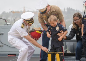180802-N-DA737-0337 SEATTLE (Aug. 2, 2018) Joe Savage, Port of Seattle Police Department Chief for a Day, dons fire-fighting equipment with the help of Capt. Stewart Bateshansky, executive officer of amphibious transport dock ship USS Somerset (LPD 25), Marine Corps Chief Warrant Officer Mathew Hansen, and his mother, Michele Shepard. Somerset is in port in Seattle for Seafair Fleet Week, an annual celebration of the sea services wherein Sailors, Marines and Coast Guard members from visiting U.S. Navy and Coast Guard ships and ships from Canada make the city a port of call. (U.S. Navy photo by Mass Communication Specialist 2nd Class Jonathan Jiang/Released)