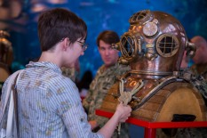 180802-N-SH284-0028 SEATTLE (August 02, 2018) A visitor at the Seattle Aquarium inspects a dive helmet at a static display presented by the Naval Station Everett dive locker during the 69th annual Seafair Fleet Week. Seafair Fleet Week is an annual celebration of the sea services wherein Sailors, Marines and Coast Guard members from visiting U.S. Navy and Coast Guard ships and ships from Canada make the city a port of call. (U.S. Navy photo by Mass Communication Specialist 2nd Class Vaughan Dill/Released)
