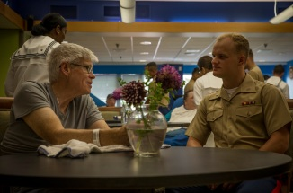 180803-M-OI329-1008 SEATTLE (Aug. 3, 2018) U.S Marine Corps 1st Lieutenant Samuel Banks speaks with a veteran at the Veteran's Affairs Puget Sound Health Care System during Seafair Fleet Week in Seattle. Seafair Fleet Week is an annual celebration of the sea services wherein Sailors, Marines and Coast Guard members from visiting U.S. Navy and Coast Guard ships and ships from Canada make the city a port of call. (U.S. Marine Corps photo by Cpl. Joseph Prado)