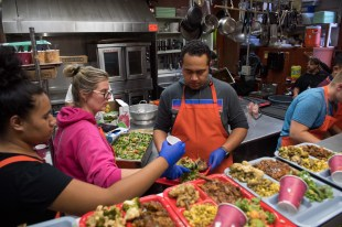 180803-N-DA737-0186 SEATTLE (Aug. 3, 2018) Hospital Corpsman 1st Class Jonathan Faletoi (right), assigned to Naval Hospital Bremerton, prepares meals with his wife, Stephanie, (middle), and sister, Patricia, (left), at Bread of Life Mission during a Seattle Seafair Fleet Week community relations event. Seafair Fleet Week is an annual celebration of the sea services wherein Sailors, Marines and Coast Guard members from visiting U.S. Navy and Coast Guard ships and ships from Canada make the city a port of call. (U.S. Navy photo by Mass Communication Specialist 2nd Class Jonathan Jiang/Released)