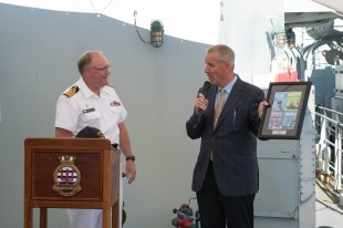 180804-N-DA737-0083 SEATTLE (August 4, 2018) Capt. Steve Jorgensen, deputy commander of Canadian Fleet Pacific, receives a commemorative print of the 2018 Seattle Seafair posters from Seafair President and CEO Richard Anderson during a reception held aboard Kingston-class coastal defense vessels HMCS Whitehorse (710) and HMCS Yellowknife (706) during Seattle's Seafair Fleet Week. Seafair Fleet Week is an annual celebration of the sea services wherein Sailors, Marines and Coast Guard members from visiting U.S. Navy and Coast Guard ships and ships from Canada make the city a port of call. (U.S. Navy photo by Mass Communication Specialist 2nd Class Jonathan Jiang/Released)
