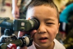 180805-M-ST406-1094 SEATTLE ( August 5, 2018) A child looks into the sight of a grenade launcher during a tour aboard amphibious transport dock ship USS Somerset (LPD 25) during Seattle Fleet Week. Seafair Fleet Week is an annual celebration of the sea services wherein Sailors, Marines and Coast Guard members from visiting U.S. Navy and Coast Guard ships and ships from Canada make the city a port of call. ( U.S. Marine Corps photo by Lance Cpl. Ana S. Madrigal)