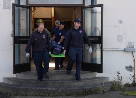 181108-N-KH214-0196 OAK HARBOR, Wash. (Nov. 8, 2018) Naval Air Station (NAS) Whidbey Island Federal Fire and Emergency Services Department personnel carry an injured bystander to a nearby ambulance while participating in a drill scenario for the anti-terrorism exercise Reliant Defense on Whidbey Island. Reliant Defense is an anti-terrorism and force-protection exercise conducted to ensure that the Navy is ready to respond to changing and dynamic threats at all times. (U.S. Navy photo by Mass Communication Specialist 2nd Class Scott Wood/Released)