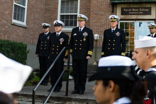181111-N-SH284-0008 BREMERTON, Wash. (Nov. 11, 2018) Capt. Alan Schrader, center, commanding officer, Naval Base Kitsap (NBK), makes a speech alongside James Willis, left, command master chief, NBK, and Cmdr. Brian Rednour, right, executive officer, NBK, in front of the Naval Base Kitsap quarterdeck during a bell ringing ceremony to commemorate the 100th anniversary of the end of the first world war. The ceremony celebrated the 100th anniversary of the signing of the armistice that ended the war and featured a tolling of the bells, with 21 bell strikes to honor those who served and sacrificed during the war. (U.S. Navy photo by Mass Communication Specialist 2nd Class Vaughan Dill/Released)